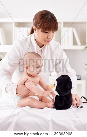 Female Doctor Pediatrician Playing With Patient Baby