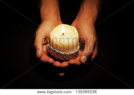 Praying Hands with candle in dark background