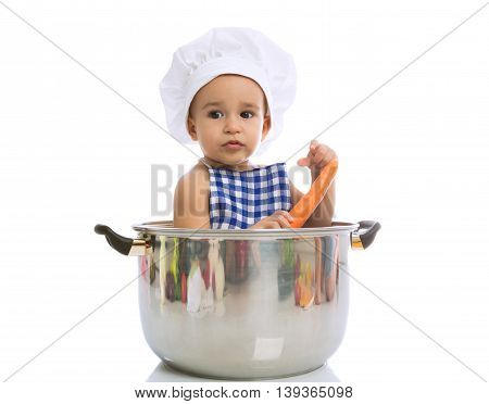 Adorable Baby Sitting In A Chef's Pot And Holding Fresh Carrot