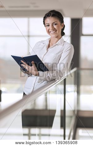 Strong confident business woman standing in an office building hallway holding a note pad preparing for a meeting