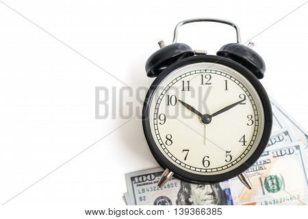 Selective focus top view of black vintage antique alarm clock on dollar money cash isolated on white background - concept of time and financial management