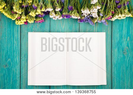 Beautiful Colorful Flowers And Open Blank Book On A Blue Wooden Table