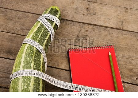 Marrow, Measure Tape And Red Notepad On Brown Wooden Table