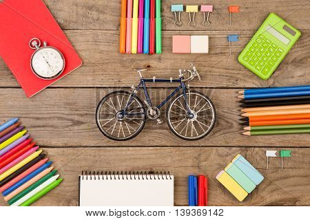 Bicycle Model, Stopwatch, Calculator, Notepads And Other Stationery On Brown Wooden Table
