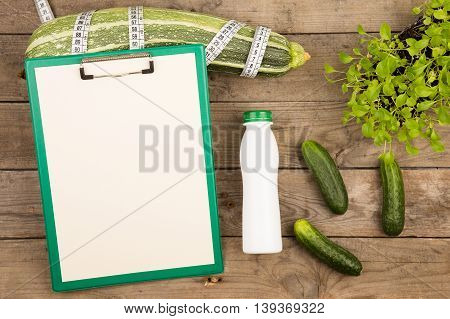 Marrow Squash, Measure Tape, Blank Clipboard, Bottle Of Water And Cucumbers On Brown Wooden Table