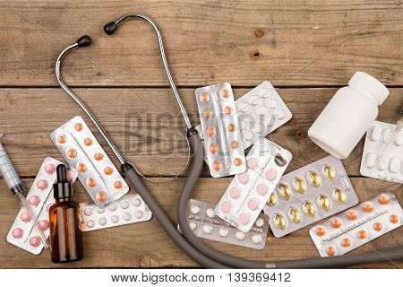 Pills, Medical Bottle, Syringe And Stethoscope On Brown Wooden Table