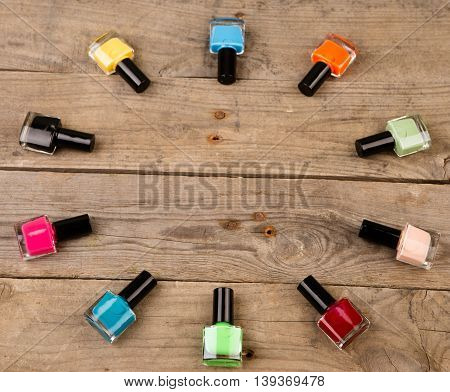 Coloured Nail Polish Bottles Stacked Circle On Brown Wooden Table