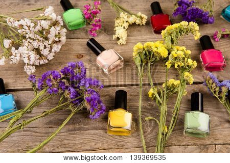 Bottles Of Colorful Nail Polish And Flowers On Brown Wooden Table