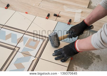Laying colored ceramic tiles on the concrete floor in the living room of a city apartment. In working hands holding a hammer debugging.