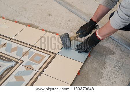 Worker tiler lays tiles. The hands holding the hammer debugging. Living room large apartment. Between the tiles adaptation for smooth clearance.