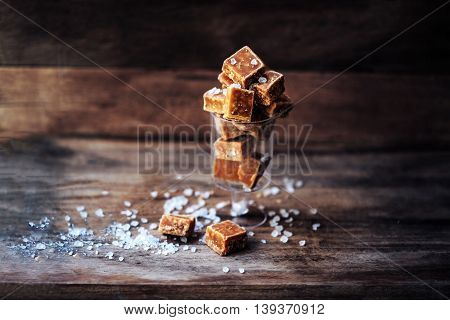 Salted caramel pieces and sea salt macro. Butter caramel candy macro. Vintage rustic style