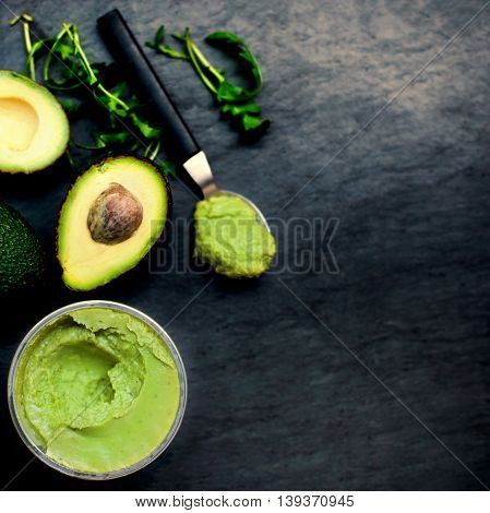 Halved avocado spread pasta. Top view avocados with Traditional Mexican sauce Guacamole on black background