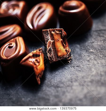 Chocolate over black background. Chocolate Candy Cocoa. Assortment of fine chocolates close up