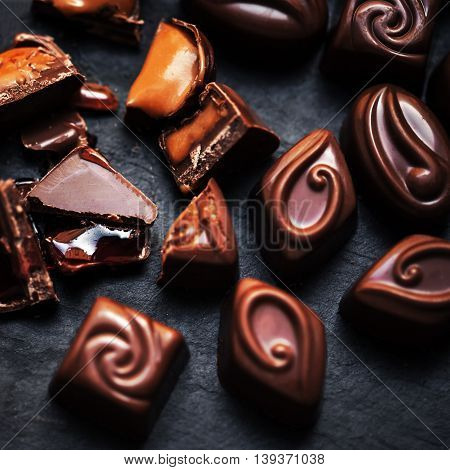 Chocolate candy close up on dark background. Chocolate Candies Cocoa. Assortment of fine chocolates