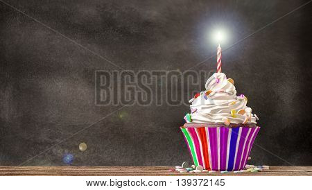 Cupcake with cream candies and a candle on a wooden table with a blackboard background. Empty free copy space available. 3D Rendering