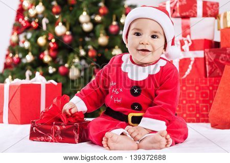 Happy Cute Smiling Little Santa Claus Baby With Gifts And Christmas Tree