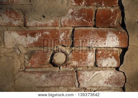Obsolete red plastered brick wall with rusty pipe