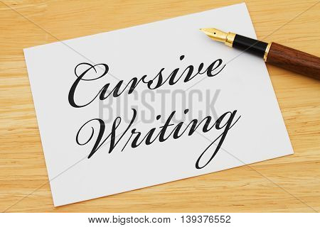 Learning how to write cursive White Greeting card with text Cursive Writing on a wood background