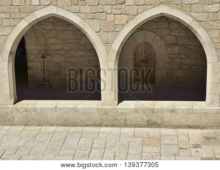GUIMARAES, PORTUGAL - AUGUST 9, 2016: Stone arches of the corridor at the inner patio of Palace of the Dukes of Braganza in Guimaraes in the northern region of Portugal.