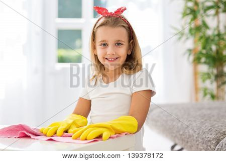 Worth smiling young girl with gloves at home
