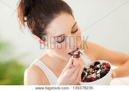 Girl having healthy breakfast with muesli and berries.
