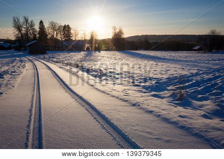 Snow dirt road at countryside Finland winter sunset