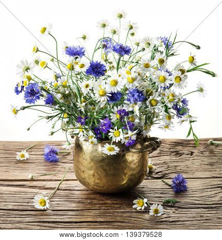Bouquet of chamomiles and cornflowers in the vase on the wooden table. White background.