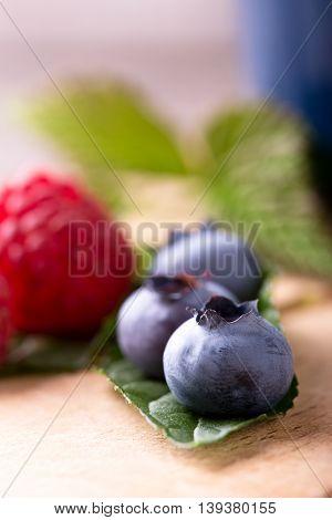 Detail Of Several Blue Blueberries On Green Leaf