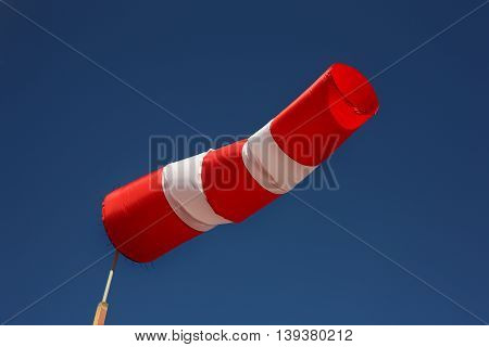 Boats parking - Wind direction indicator. Windsock the sky background. Wind west.
