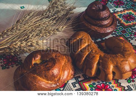Homemade baking. Cheesecake with cherry croissant with jam bun Snail with poppy seeds and barley spikes on the embroidered tablecloth in ethnic style.