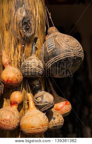Carved decorative African gourds hanging on post