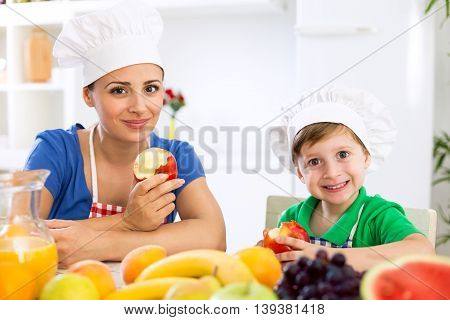 Smiling Happy Mother And Child Enjoy And Eating Fruits