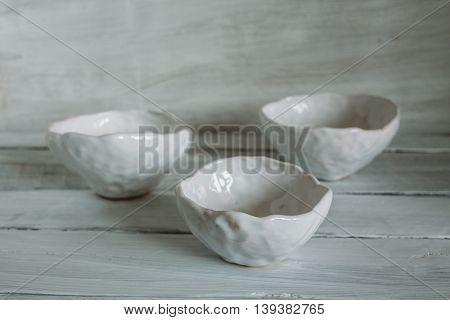 Three white bowls white clay bowls bowls of handmade clay white bowls on a light background.
