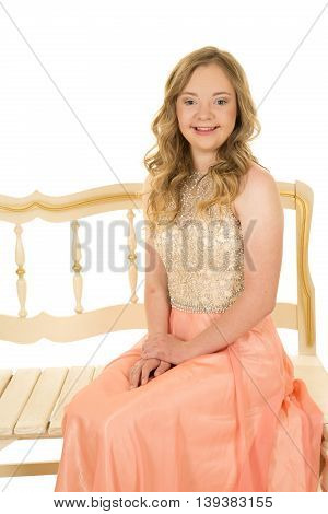 A woman with down syndrome sitting on her bench with a smile on her face.