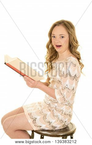 A woman with down syndrome holding onto a book with a shocked expression.