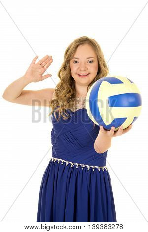 A woman with down syndrome in her fancy dress with a volleyball and smile.