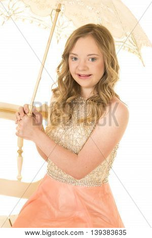 A woman with down syndrome in her vintage dress with an umbrella.
