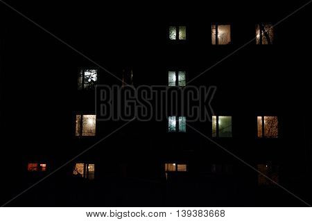 Brightly illuminated windows of multistory building at night