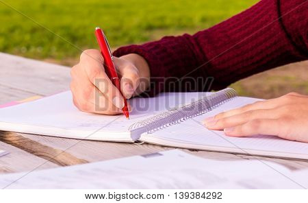 outdoors at a wooden table female hand writing in a notebook, burgundy sweater, green grass in the background, the book lying next,