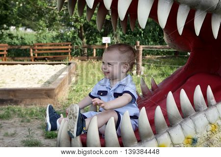 Portrait of child in jaws of dinosaur