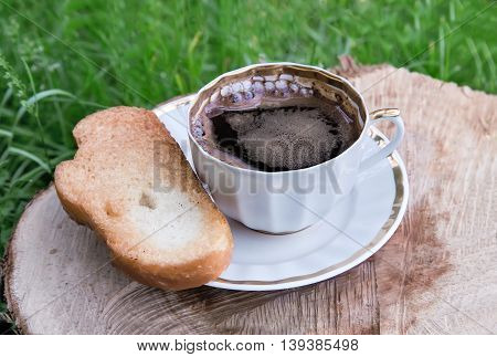 In the garden on the stump of a sawn tree trunk is a black Cup of coffee. Next on the plate are toasted white bread.