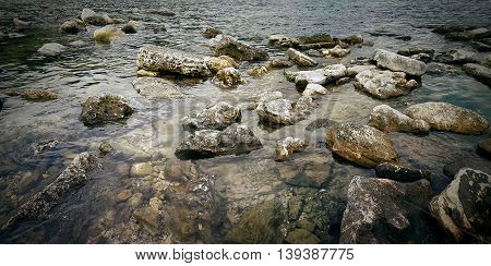 Underwater texture of a rocky seafloor with stone pieces
