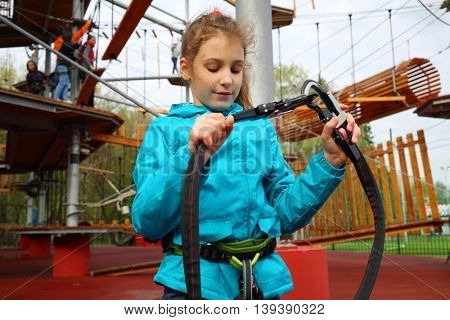 Happy pretty girl holds safety rope near Rope way on special playground