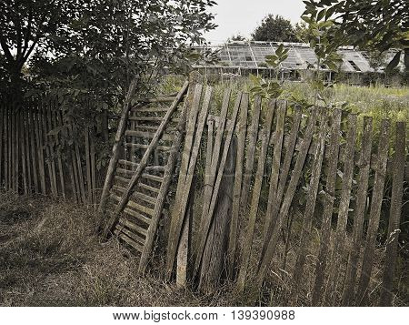 evening photo with beautiful devastated wooden fence with ruin of a greenhouse on the background in the village Hostenice in Ceske stredohori region in Czech republic