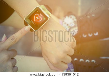 High angle view of female forefinger pressing the button on smart watch with heart rate app while sitting on a bench in the park. Modern technology and healthy lifestyle concepts.