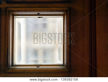 square windows in the old door. Glass with bevel
