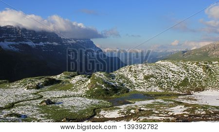 Green meadow with pond valley and mountains. New snow in summer. Swiss Alps.