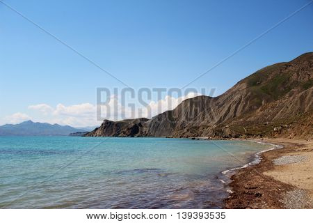 Seascape at sunrise, mountains, gravel beach Crimea