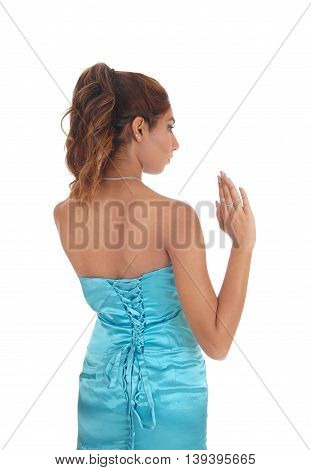Slim young woman standing in a blue dress from the back holding up one hand isolated for white background.