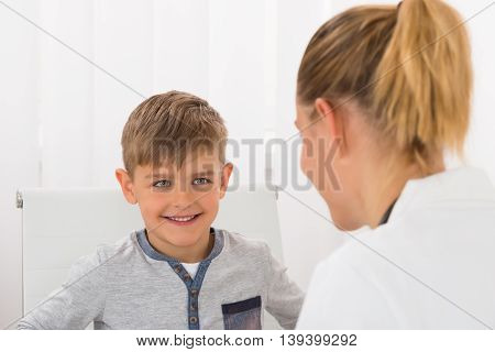 Portrait Of A Boy Smiling At Female Doctor In Clinic